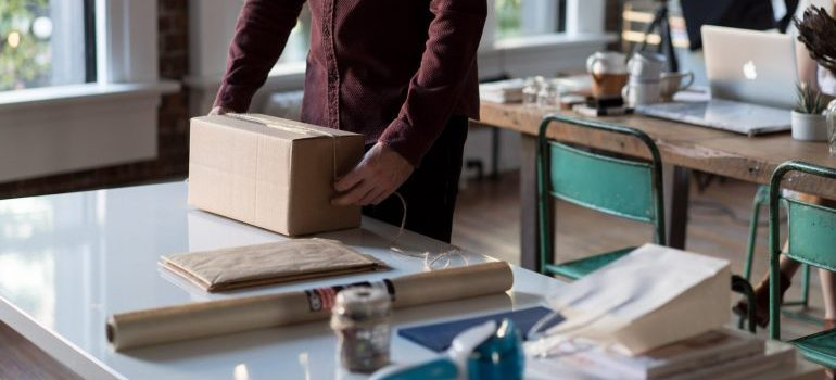 negotiate with logistics companies- a man packing a box