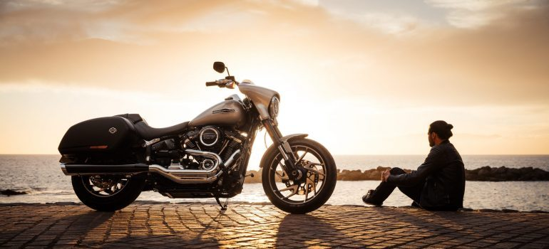 A motorcycle and a man sitting next to it