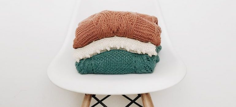 Wool sweaters folded on a chair