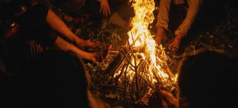 People around the bonfire sharing their experiences about settling in a new country