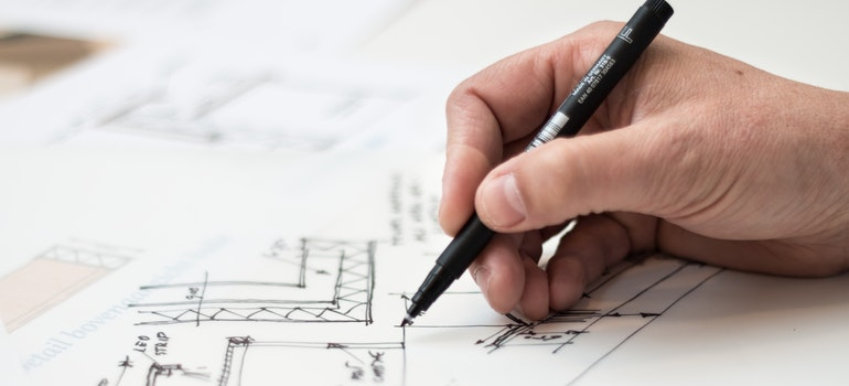 A hand drawing a plan for project cargo shipping with a black marker