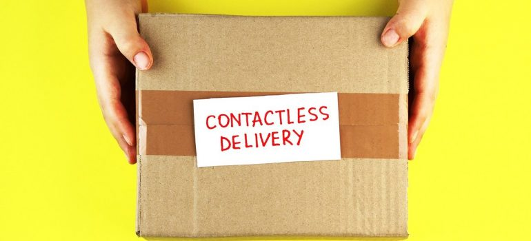 """a person hold a box with a piece of paper that reads """"contactless delivery"""""""