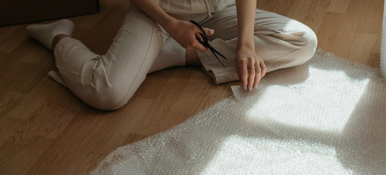 Woman cutting bubble wrap to protect shipments from cold weather