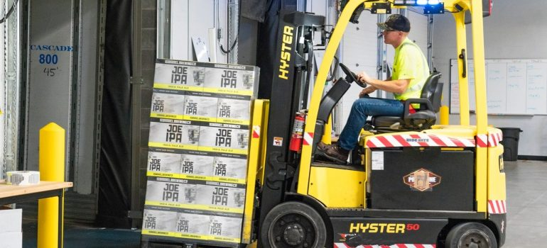 an employee driving a forklift in a wearhouse