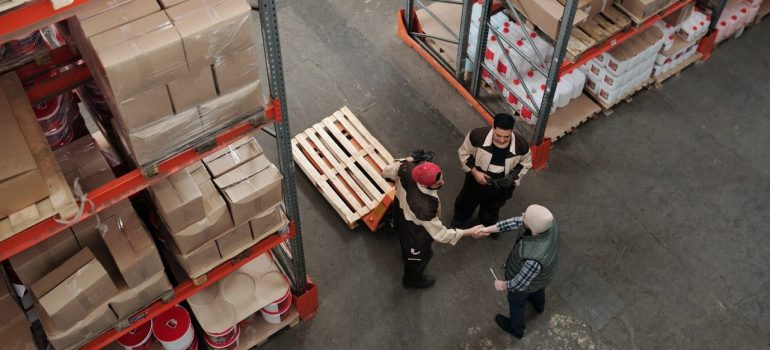 three men shaking hands while one is using a manual stroller as a way to reduce carbon footprint in logistics